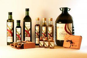 Many different olive oil bottles on a white surface.