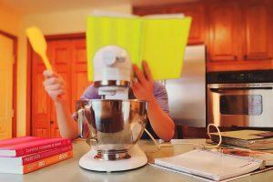 A person behind a yellow book in a kitchen, standing in front of some kitchen appliance.