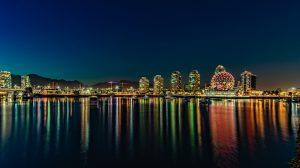 An image of Vancouver at nighttime. The picture is that of a city seen from some boat on a body of water. Moving to Canada means enjoying all the benefits this city has to offer.