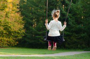 A girl in a white shirt, black skirt and pink rain-boots on a swing in some natural setting.