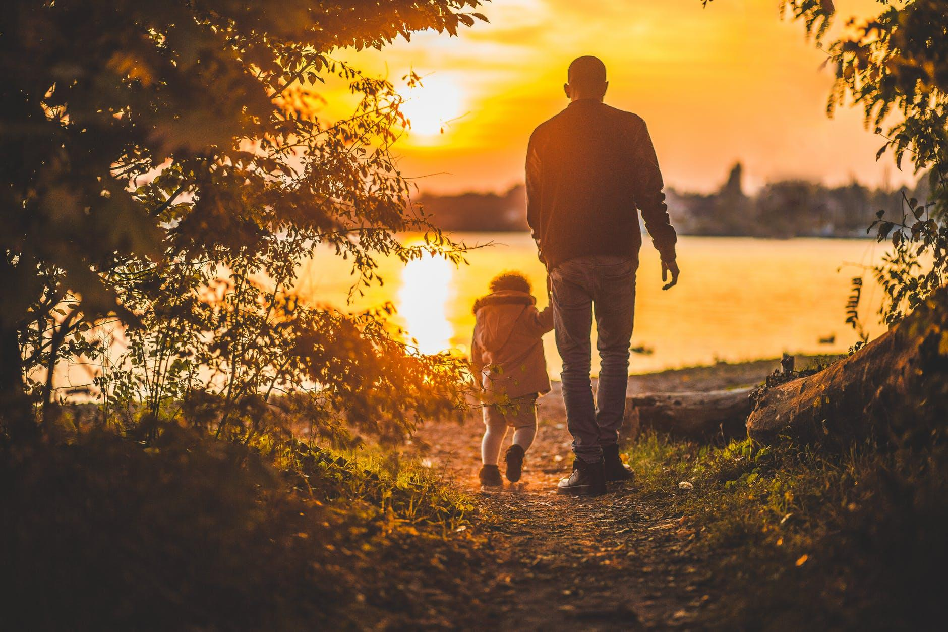A photo of a man and a child in nature during sunset. By moving to Toronto with a family, you get to marvel at the sight of the amazing Canadian landscape.