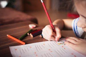 A child writing something with a red pen. Moving during the school year implies transporting all of your child`s school supplies.