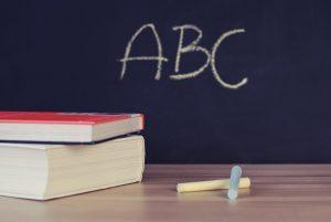 A blackboard with abc written on it. two books and some yellow and blue chalk.