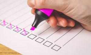 A close up of a person holding a pink marker and ticking off items on a checklist.