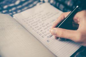 A close up of a person holding a pen and creating a checklist. Learn how to make a moving checklist as soon as possible in order to make the relocation process less difficult.