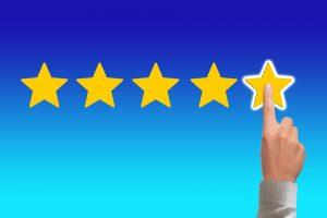 Five yellow start on a blue background. A human hand is pointing and touching the last star in the row.