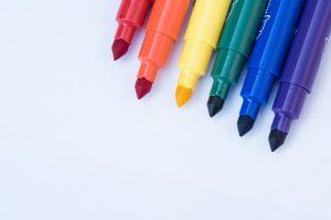 Six different colored markers on a white surface.