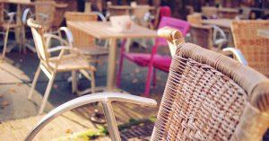 A few brown chairs and a pink chair in a restaurant.