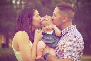 Parents holding and kissing their baby girl.