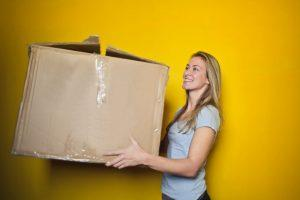 A woman holding a big cardboard box and standing in front of a yellow wall. She is smiling and wearing a grey t-shirt.