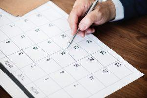 A calendar and a person`s hand holding a pen. He might be marking a certain date in the calendar, and panicking that he has to pack in 7 days.