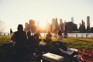 A group of friends on a picnic, which is one of the best outdoor activities in Toronto. We see the city behind them.