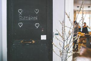 A black door with the word bonjour written on it, which you will see a lot after moving home to Montreal.