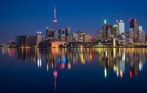 A view of the buildings in Toronto during night, seen from a body of water.