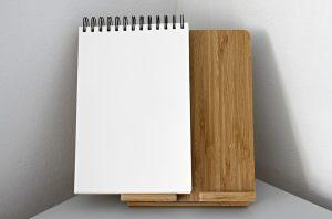 A white notepad on a brown paper stand.