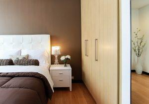 A picture of a bedroom, including the closet, an end table, the bed and a lamp.