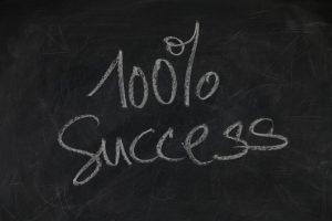 100% success written on a blackboard.
