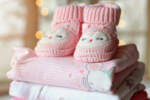 Pink baby boots and pink baby clothing.