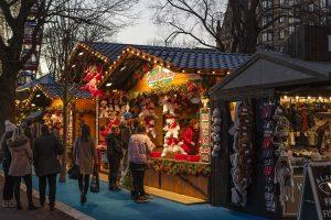 A few people at a Christmas market, and visiting it is one of the things to do during fall in Toronto.