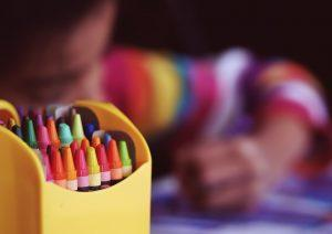 A close up of a box of crayons and a child behind it.
