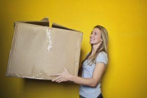 A woman with a box on a yellow background keeping of her moving timeline