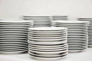 Stacks of white plates, to be included in your packing checklist.