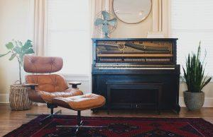 An antique piano in a living room.