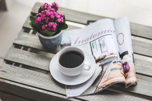 A magazine and a cup of coffee on the table.